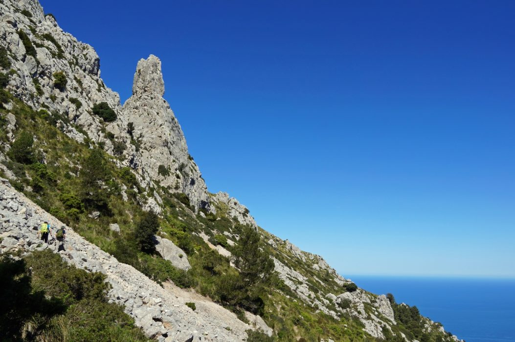 Walkers cross steep boulder scree on the rugged slopes of Galatzó