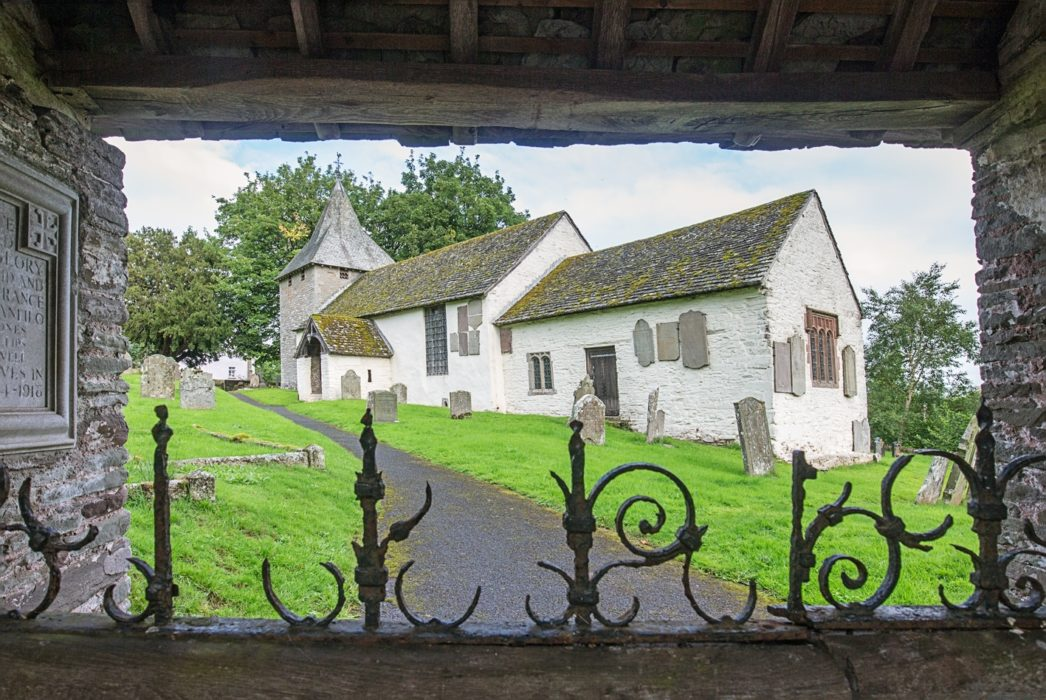 The well-preserved Norman and medieval church in Llanfilo viewed through the lychgate