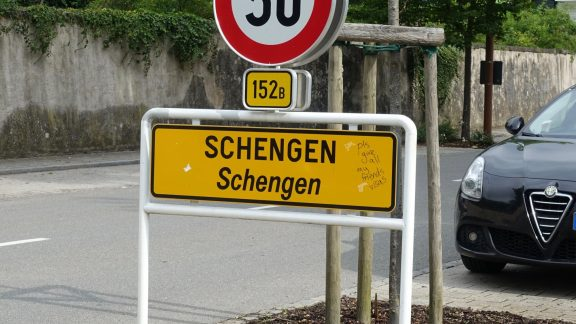 City limit sign for Schengen (with graffito requesting visas)