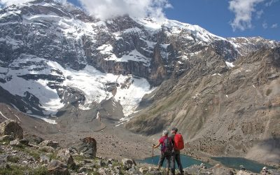 Trekkers enjoy the scenery, looking up the huge north face of Mirali Peak