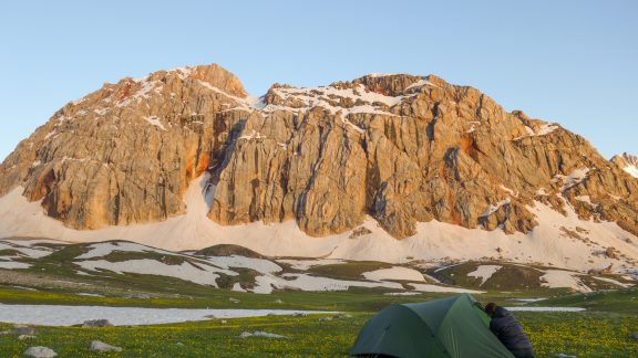 Camping at its best. Green grass, alpine flowers and a jagged mountain in the distance. What's not to like?