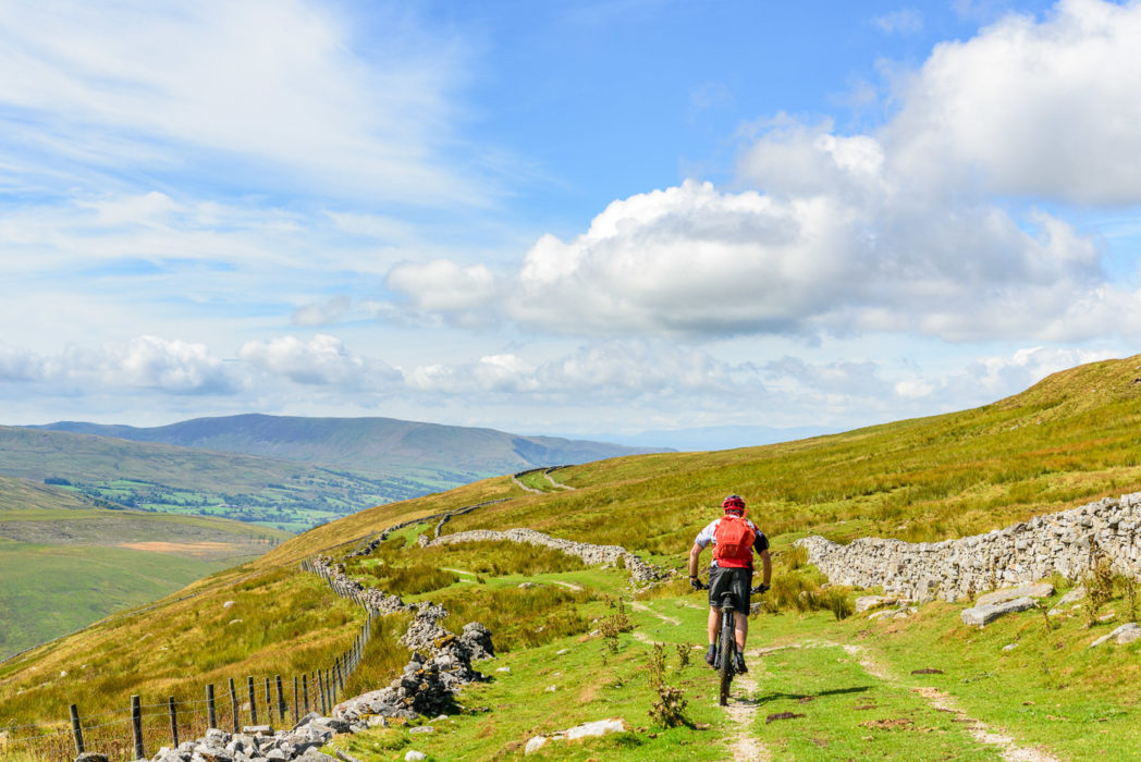 Jon Sparks on the 'Driving Road' during our Pennine Bridleway ride, with Dentdale appearing below, Middleton Fell behind and the Coniston Fells on the skyline.