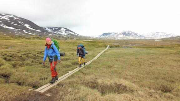 4 Walkers heading for Alesjaure, boardwalks are common in boggy areas.