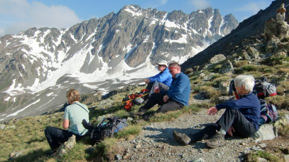 Walkers relax on the Furcletta pass above the Tuoi Hut
