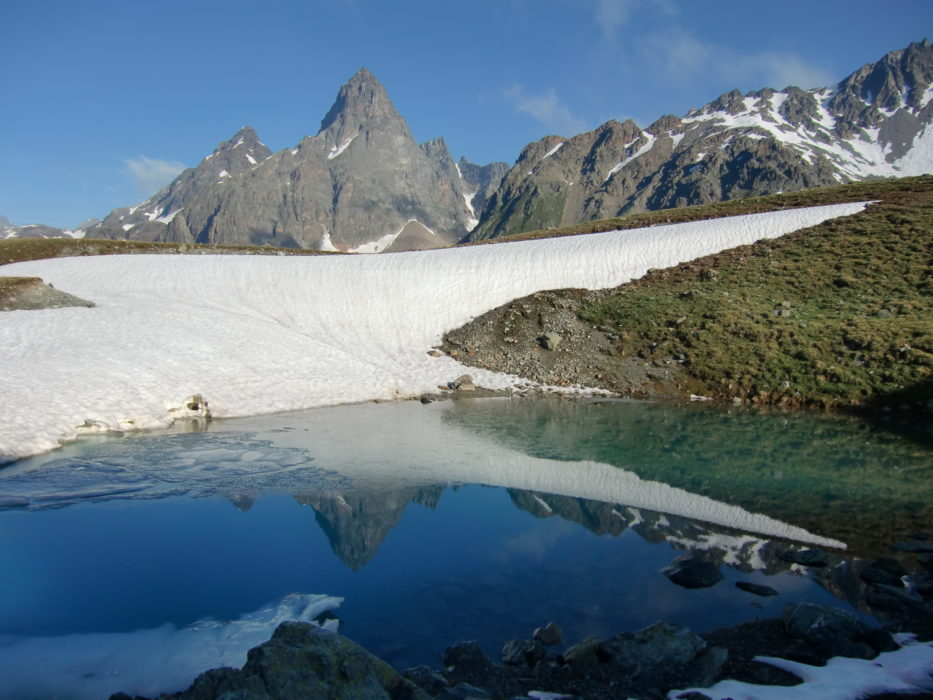 The rocky cone of Piz Buin is reflected in an icy pool near the Furcletta pass