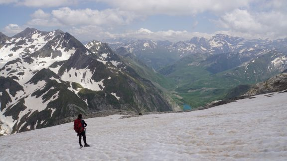 Descending on the glacier with Lac du Barrage d'Ossoue below and the Cirque de Gavarnie peaks in the distance