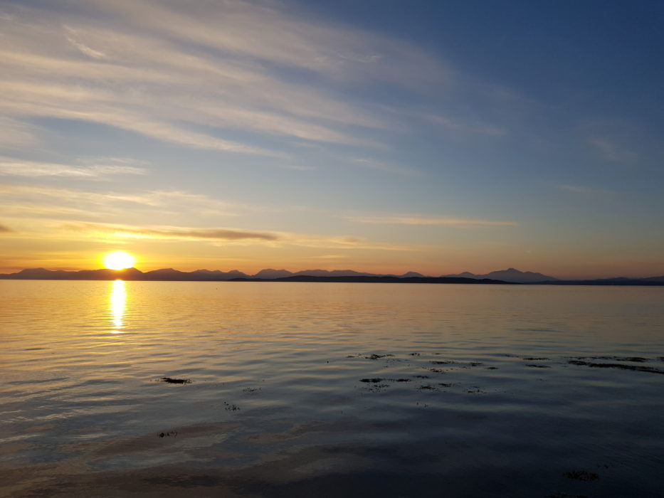 The sun rises over Ben Nevis, from the east coast of Mull