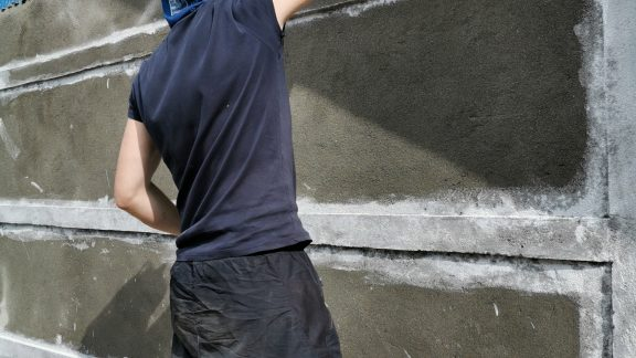 Ioan painting the side of the school