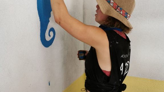 Sarahann painting murals inside the classrooms