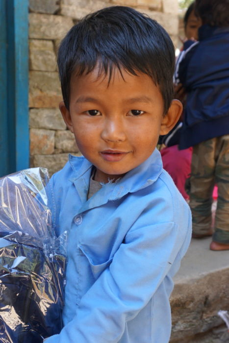 A child at Kinja holding his new uniform