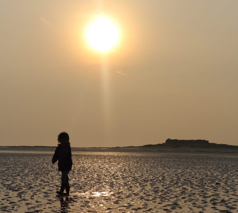 child in sunset on tidal flats