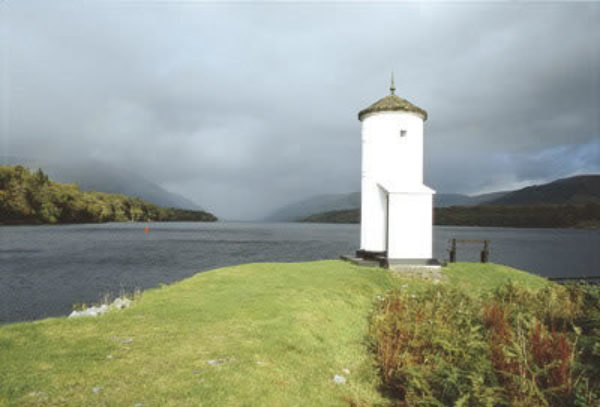 A whitewashed pepperpot lighthouse marks where the Caledonian Canal joins Loch Lochy near Gairlochy.